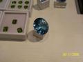 В центре большой голубой топаз (около 200 карат), а рядом зеленые камни - это хризолит.